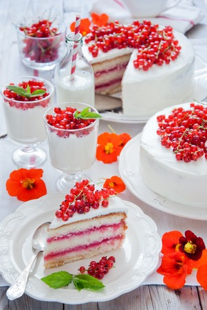 dessert stand: Cakes with red currant decorated with fresh red berries, cream desserts with berries and mik