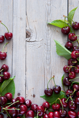 no food: Frame from red cherries on a light wooden background Stock Photo