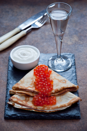 shrove: Blini with red caviar  and Vodka on a dark wooden background Stock Photo