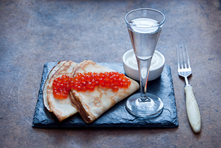 blini: Blini with red caviar  and Vodka on a dark wooden background Stock Photo