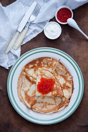 blini: Blini with red caviar on a dark wooden background