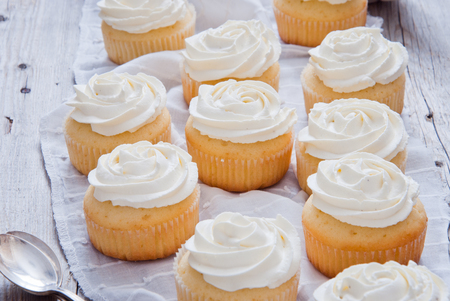Homemade Cupcakes with vanilla cream on a wooden background