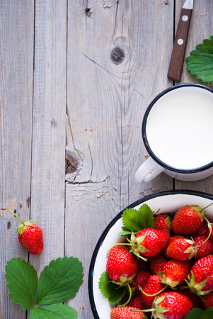 Fresh Organic Strawberries in white bowl and milk on a wooden background