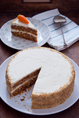 Homemade Carrot Cake with pecans, butter cream on a white plate Stock Photo