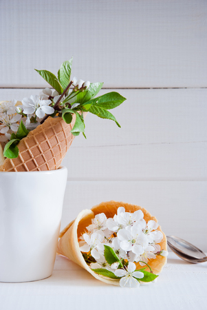 Fresh flowers in ice cream cone still life on a light wooden background Imagens