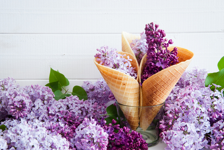 Purple flowers of lilac  in ice cream cone still life on a light wooden background 스톡 콘텐츠