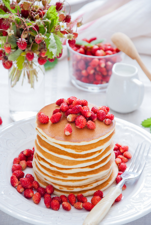 Stack of Pancakes with Wild Strawberries on a white plate