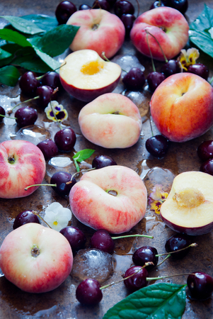 Fresh peaches and cherries on brown wooden background