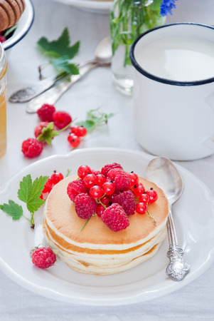 Homemade Pancakes with fresh red berries and honey