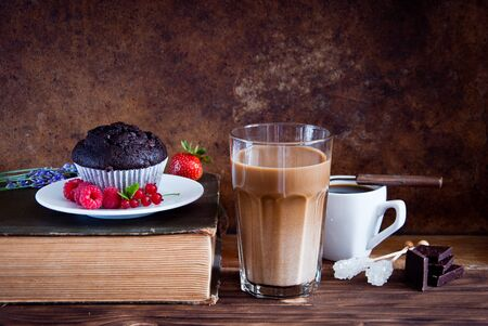 Chocolate muffin with red berries and coffee and old books