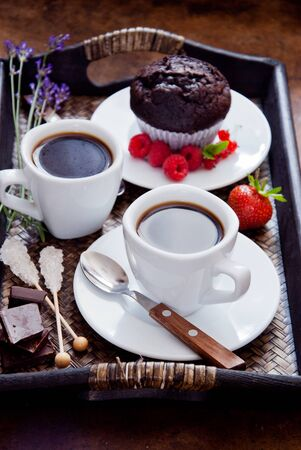 Black coffee in white cups and chocolate muffin for breakfast Stock fotó