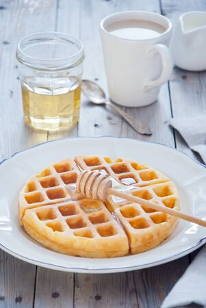 Pouring honey to Homemade waffles for breakfast