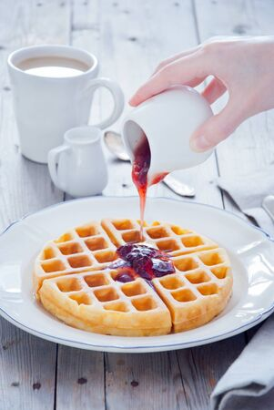 Pouring Strawberry Jam to homemade waffles for breakfast