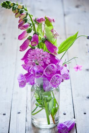 Variety of purple flowers in a glass vase on gray wooden background