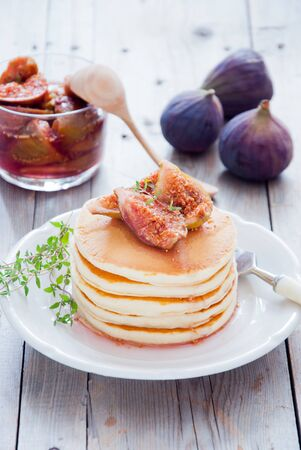 A stack of homemade pancakes with fig jam and thyme on a white plate