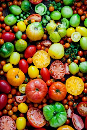 Fresh heirloom tomatoes background, organic produce at a Farmers market