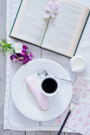 Breakfast - eclair and coffee cup with book