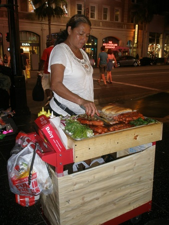 walk of fame: Hollywood, USA-August, 2012-woman cooking hot dogs on the walk of fame at night for tourists.