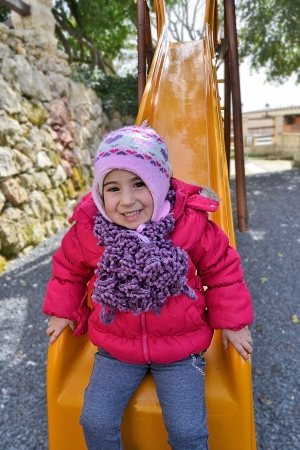 Small and beautiful girl plays outdoors photo