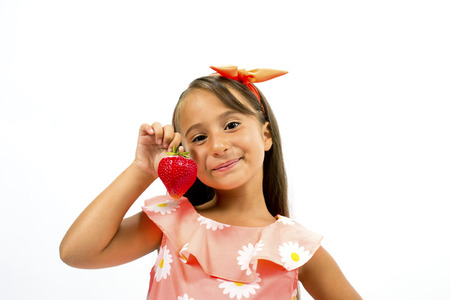 Beautiful little girl with strawberry posing smiling photo