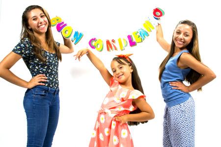 Smiling girls posing with inscription happy birthday photo