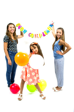 Smiling girls with balloons and happy birthday written photo