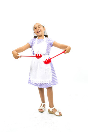 Adorable little girl chef with kitchen utensils and cap photo