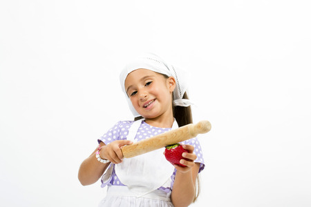 Small smiling chef with kitchen utensils and strawberry photo