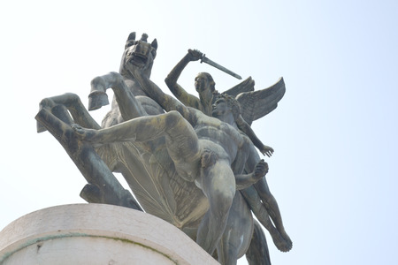 from below: Bronze statue shot from below with sky background
