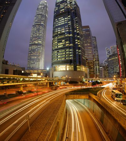 Night Fisheye view of IFC (International Financial Centre) in Hong Kong with curving traffic light track. photo