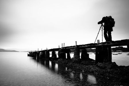 take: a man taking photo on the wooden pier, black and white