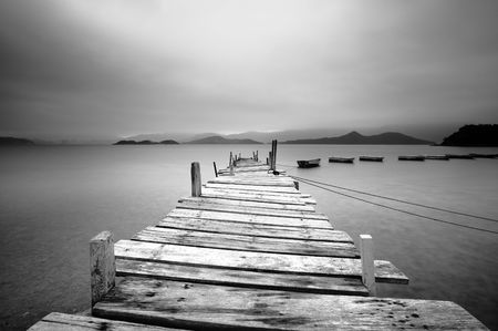dreary: Looking over a pier and boats, black and white