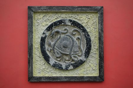 bronze Black Tortoise sculpture on a red wall  photo