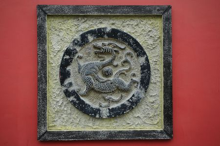 bronze dragon sculpture on a red wall  photo
