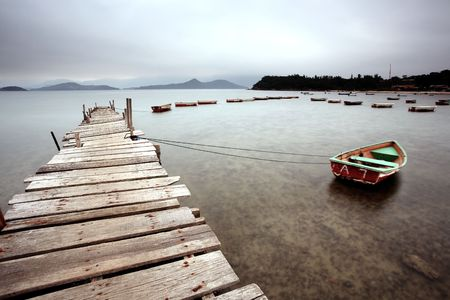 dreary: a wooden pier and boats Stock Photo