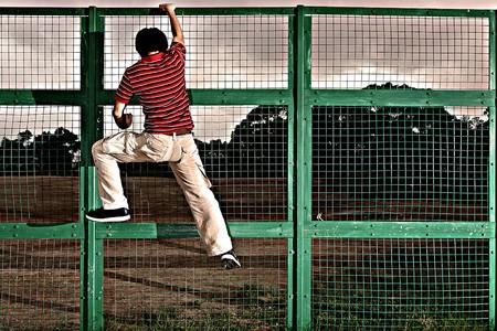 barbed wires: hombre de escalada en la valla de alambre de p�as