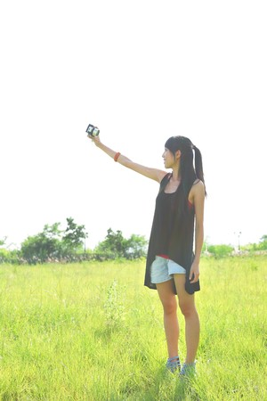 woman taking a photo of herself outdoor in soft color tone photo