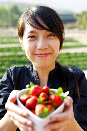 smile girl give you bowl of strawberries photo