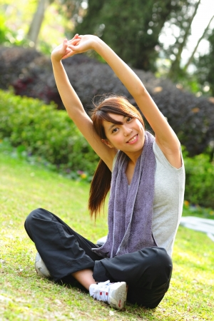 woman doing stretching exercise in park photo