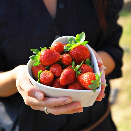 strawberry in heart shape bowl with hand photo