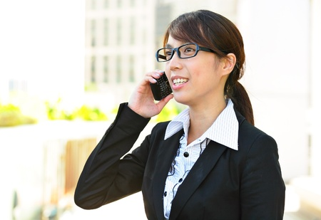 Business woman sending a text message on mobile phone photo