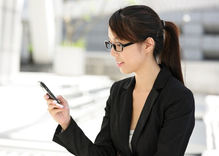 Business woman sending text message on mobile phone Stock Photo - 9996240