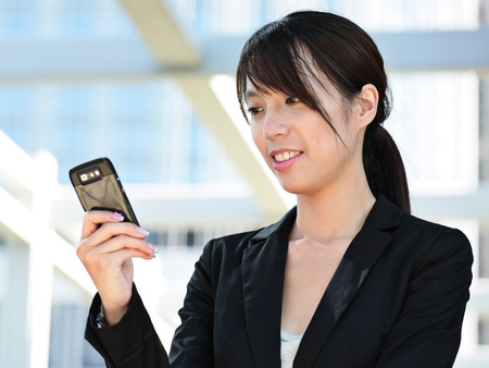 Business woman sending text message on mobile phone photo