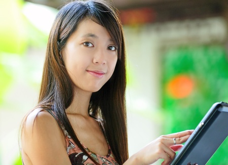 Beautiful young woman using tablet touch computer photo