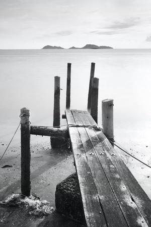 pier go into sea , black and white photo
