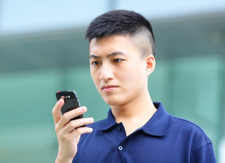 Man typing text message on mobile phone photo