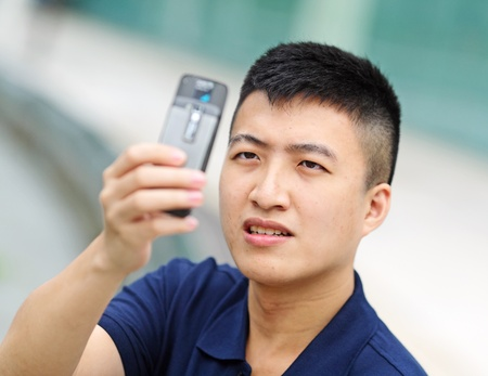 young man taking picture with mobile phone photo
