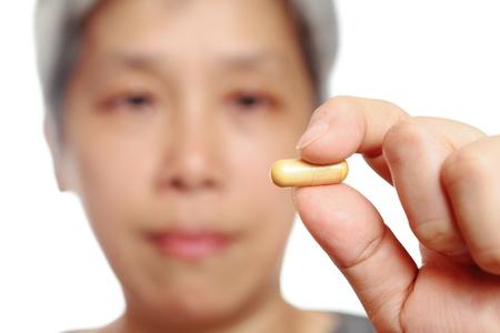 mature woman holding pill photo