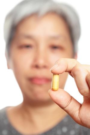 mature woman holding pill Stock Photo - 10847695