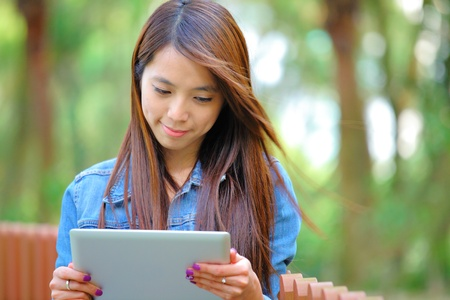 young asian woman with tablet computer outdoor photo